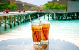 Iced tea against tropical Overwater Bungalow Resort.