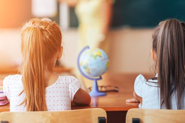 Two little schoolgirls sit at a desk in a school class...