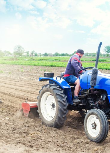 A farmer on a tractor cultivates a farm field. Soil...