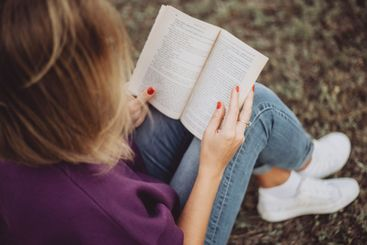 cute girl reading a book while sitting on the grass in...