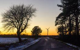 Solnedgång med väg och vindkraftverk