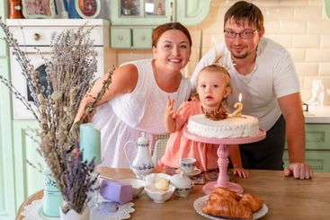 baby girl with a cake in kitchen at home. family home...