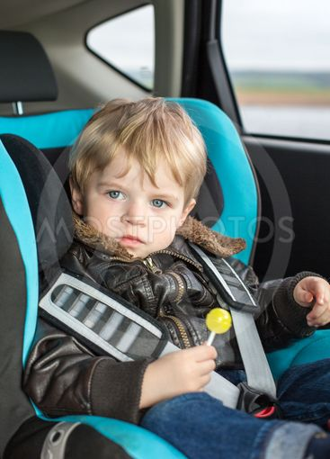 Toddler in safety car seat eating candy