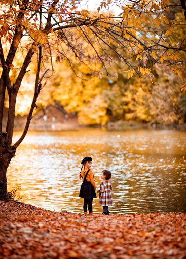 little girls standing on river bank in autumn park