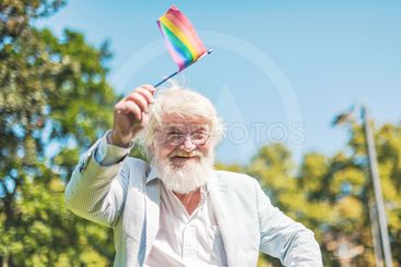 Old man waving the pride flag during the pride parade in...