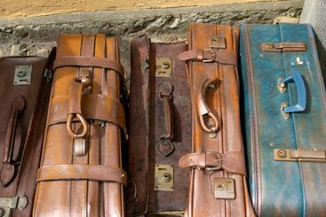 Old leather suit cases standing by a wall.
