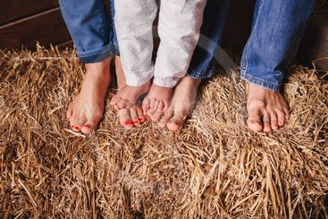 Bare feet of family members-mother, father and baby on...